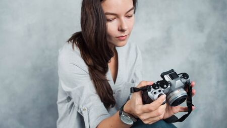 photographer takes the photo. Young successful woman photo blogger. Girl with a modern camera in hand, the photographer on a gray background