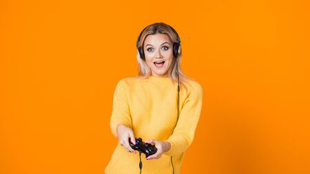 Computer games, concept. Girl uses gamepad to play on console or PC. A young woman with a gamepad on a yellow background Stockfoto