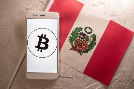 Cryptocurrency and government regulation, concept. Modern economy, smartphone with bitcoin sign on the screen on the background of the flag of Peru