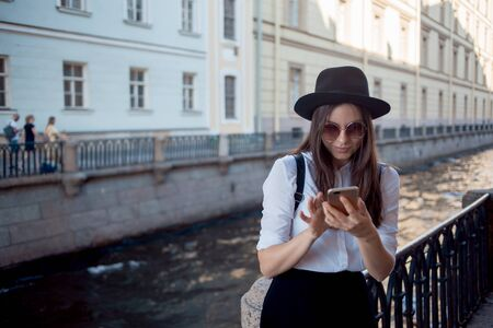 young woman in a hat and with a backpack walks in the city and uses a smartphone. Hipster on a walk uses the phone and takes photos for social networks 版權商用圖片