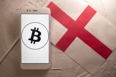 Cryptocurrency and government regulation, concept. Modern economy, smartphone with bitcoin sign on the screen on the background of the flag of England Stockfoto