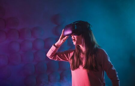 A young woman uses glasses, a virtual reality helmet on a background of a dark background in smoke. Corrects the goggles. Copyspace.
