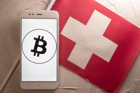 Cryptocurrency and government regulation, concept. Modern economy, smartphone with bitcoin sign on the screen on the background of the flag of Switzerland Stockfoto