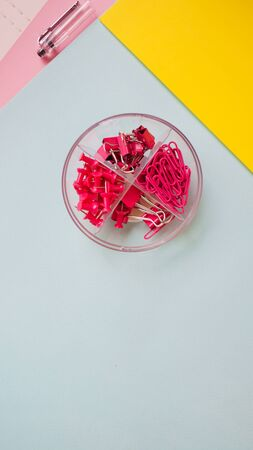 Box of paper clips on multicolored background, paper clips and paper clips. Pink paper clips on blue background