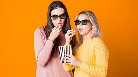 Two friends watch an interesting movie and eat popcorn. Two young female moviegoers, concept on yellow background