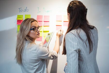 Teamwork, project management, agile methodology. Two young business women in the office are working on a startup. Colleagues plan work and stages of development of company, glue sticky leaves on Board Stockfoto