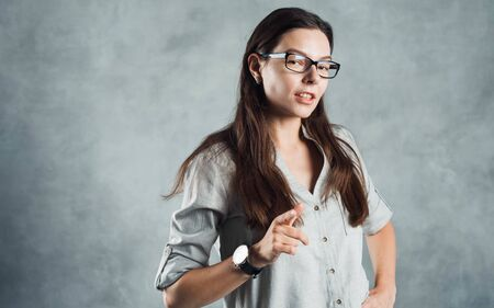 Young brunette woman in glasses, self-confidence. Smiling and calm girl on a gray textured background.