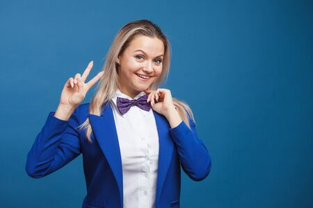 Happy smiling young woman in blue on blue background. Friendly business portrait of a young blonde woman makes a gesture of victory with two fingers up, copy space Imagens