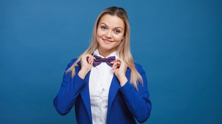 Friendly young woman in blue clothes on blue background. Blonde girl in jacket and bow tie, happy and smiling