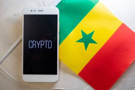 Cryptocurrency and government regulation, concept. Modern economy, smartphone with bitcoin sign on the screen on the background of the flag of Senegal,