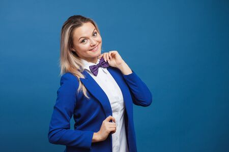 Funny business lady in a blue jacket and purple bow tie. Studio portrait on blue background, copy space
