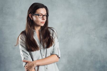 Young successful confident woman in a gray shirt against a textured gray wall. Portrait brunette in glasses, copy space on the right.