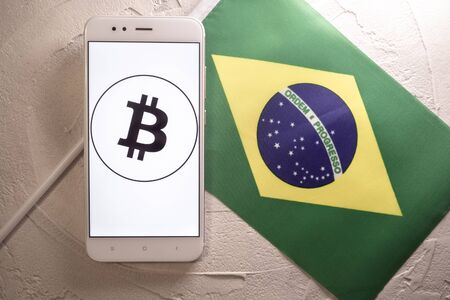 Cryptocurrency and government regulation, concept. Modern economy, smartphone with bitcoin sign on the screen on the background of the flag of Brazil