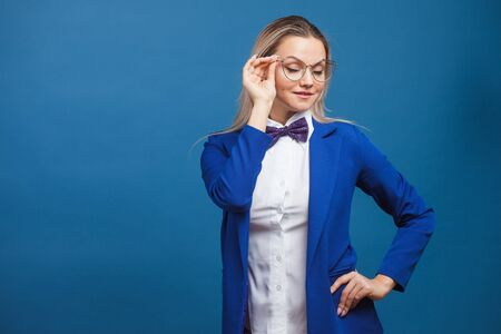 businesswoman in a stylish blue jacket and bow tie adjusts her glasses. Portrait of a young trending woman in glasses for vision