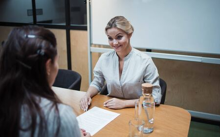 young HR woman interviews a candidate for a job. recruiter does a job interview and talks about the resume.