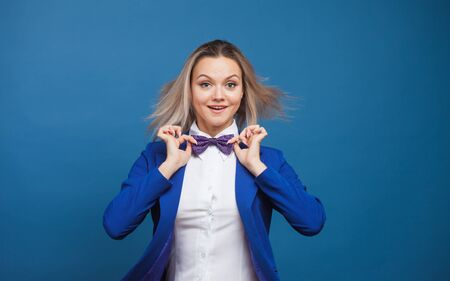 Happy smiling young woman in blue on blue background. Friendly business portrait of young blonde, copy space