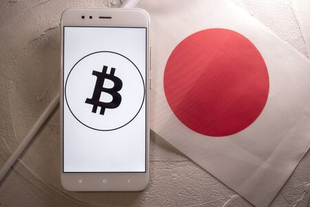 Cryptocurrency and government regulation, concept. Modern economy, smartphone with bitcoin sign on the screen on the background of the flag of Japan Imagens