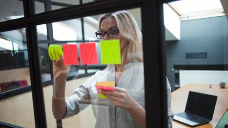 young woman in the office glues sticky sheets on the glass partition of the office. young professional woman performs a decomposition task. Project management and work planning.