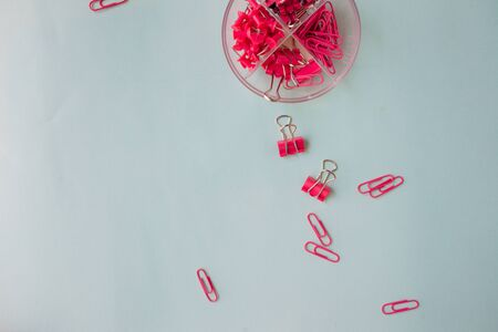 Stationery, paper clips and paper clips. Pink paper clips on blue background