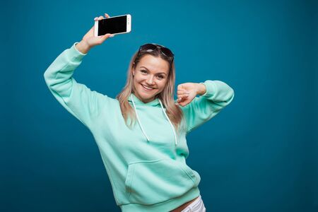 Cheerful blonde with a mobile phone. Portrait of a young positive woman in a blue hoodie on a blue background.