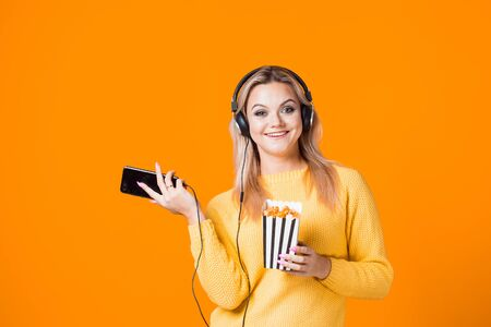 Cinema by subscription, concept. A young blonde watches movies and TV series on a streaming service.