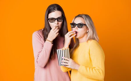 Two friends watch a movie or TV series and eat popcorn. Two young women fans of the movie, the concept on yellow background