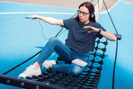 The girl, a brunette, pretty, with glasses, sits in a hammock, sways, on the playground with a bright blue coating, listening to music, dancing, relaxing, singing, trying to catch a wifi. Outdoor.