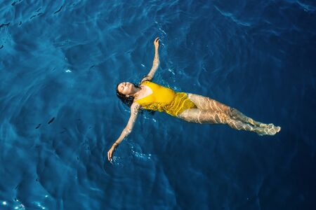 young woman in a one-piece yellow swimsuit floats on the surface of the water. Brunette girl relaxes and bathes in the blue sea, relaxing by the sea Imagens