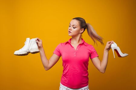 girl in a red t-shirt chooses between beautiful and uncomfortable stiletto shoes and comfortable shoes. Convenience and health vs. fashion and style, concept