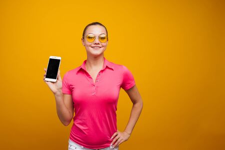 Bright and positive young woman with smartphone on yellow background. The girl uses a smartphone for communication and utility applications, the cute blonde in bright style
