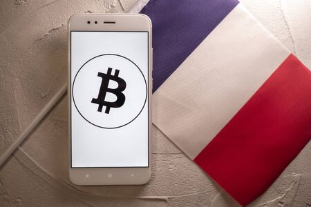 Cryptocurrency and government regulation, concept. Modern economy, smartphone with bitcoin sign on the screen on the background of the flag of France Imagens
