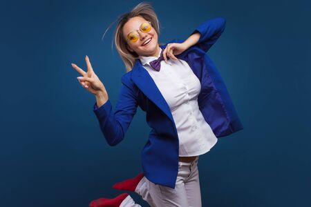 Funny business lady in a blue jacket and purple bow tie. Jumps for joy and shows a victory sign, two thumbs up. Super cool, hand gesture Imagens