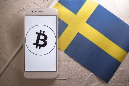 Cryptocurrency and government regulation, concept. Modern economy, smartphone with bitcoin sign on the screen on the background of the flag of Sweden Imagens