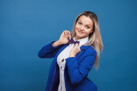 Happy smiling young woman in blue on blue background. Friendly business portrait, young blonde adjusts her bow tie