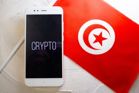 Cryptocurrency and government regulation, concept. Modern economy, smartphone with bitcoin sign on the screen on the background of the flag of Tunisia,