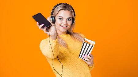 Cinema by subscription, concept. A young woman in a yellow sweater with headphones with a smartphone and popcorn in her hand. Watching movies and TV series on the streaming service. Imagens