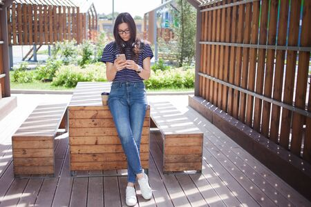 A brunette girl in glasses, with a cup of coffee, carefully checks the smartphone against the background of the cityscape in the park, standing leaning on a wooden table. Outdoor.