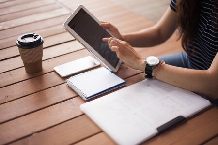 Womens hands with neat low-key manicure and with a large wristwatch, work with gadgets, tablet, smartphone, business papers lying on a wooden table. Nearby is a paper cup of coffee. Side view.