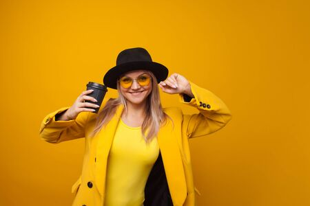 Take-away coffee. Stylish trendy young woman in bright clothes on a yellow background. A cool blonde girl in a yellow jacket, yellow sunglasses and a black hat drinks coffee and is happy