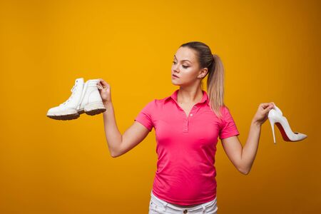 young woman chooses between beautiful and uncomfortable stiletto shoes and comfortable shoes. Comparison of the shoes, yellow background
