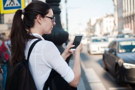 Call a taxi using the mobile application. A young woman in the city stands near the road with a smartphone in her hand and waiting for a taxi, Imagens