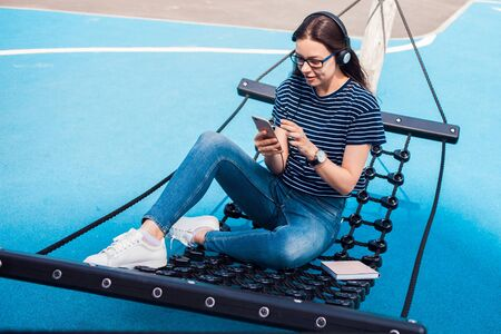 The girl, a brunette, pretty, with glasses, sits in a hammock, sways, on the playground with a bright blue coating, listening to music, dancing, relaxing, singing, trying to catch a wifi. Outdoor. Archivio Fotografico - 134681243