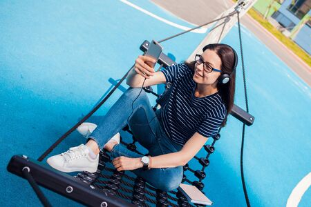 The girl, a brunette, pretty, with glasses, sits in a hammock, sways, on the playground with a bright blue coating, listening to music, dancing, relaxing, singing, trying to catch a wifi. Outdoor. Archivio Fotografico - 134681245