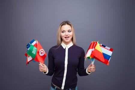 Allegra giovane donna con un ampio set di bandiere di diversi paesi del mondo. poliglotta, e imparare le lingue straniere