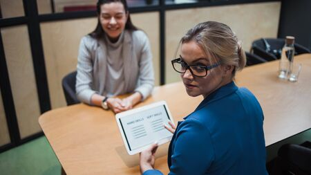 Job interview. The recruiter holds a tablet with a check list of the necessary skills of the candidate. Hard skills and soft skills, concept Foto de archivo - 135214087