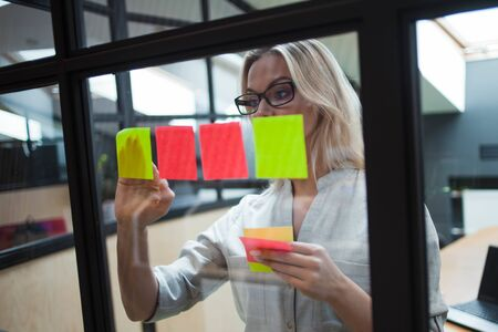 Happy and confident girl Manager plans to work on the project. young business woman wearing glasses inside a bright office with a glass partition glues colored leaves for effective project management. Reklamní fotografie