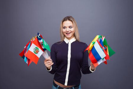 Cheerful young woman with a large set of flags of different countries of the world, tourism and travel, geographical knowledge 스톡 콘텐츠