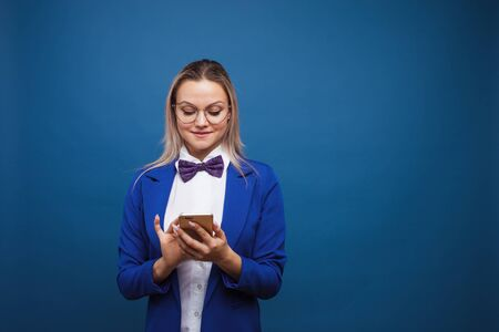 Cute and funny businesswoman in a stylish blue jacket and bow tie uses a smartphone. Girl in suit with mobile phone uses social media Stock fotó