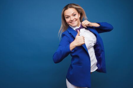 Funny business lady in a blue jacket and purple bow tie. jumps for joy and gives a thumbs up. Super cool, hand gesture