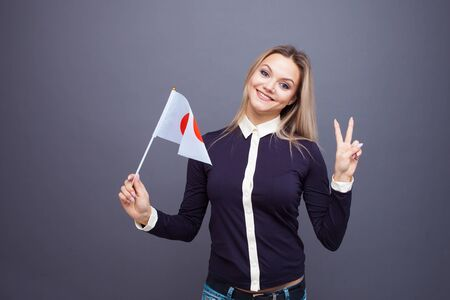 Immigration and the study of foreign languages, concept. A young smiling woman with a Japan flag in her hand. Girl waving a Japanese flag on a gray background 스톡 콘텐츠